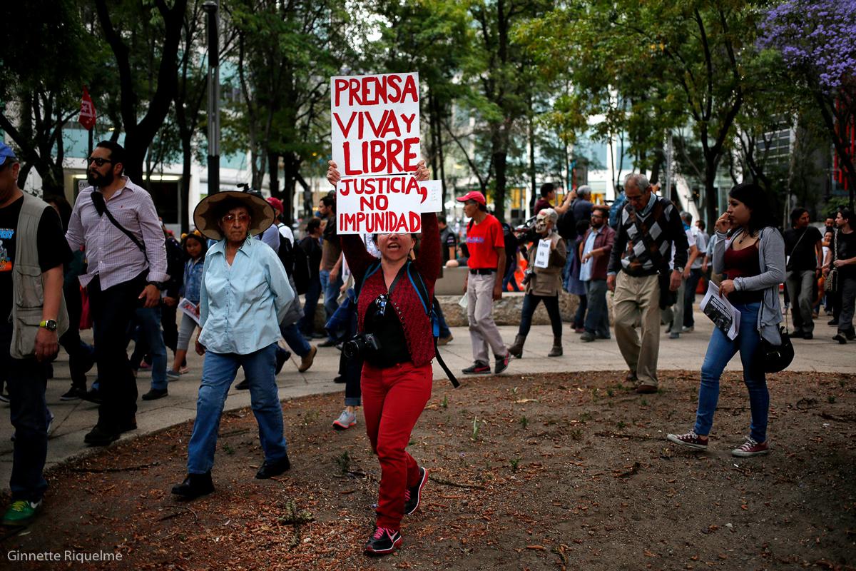 """Una mujer levanta unas pancartas: """"Prensa Viva y Libre"""" y """"Justicia, No Impunidad"""" durante una manifestación en repudio por el asesinato de la periodista mexicana Miroslava Brech, afuera de la Procuraduría General de la República (PGR) en Ciudad de México, México, marzo 25, 2017.  (FOTO: Ginnette Riquelme)"""