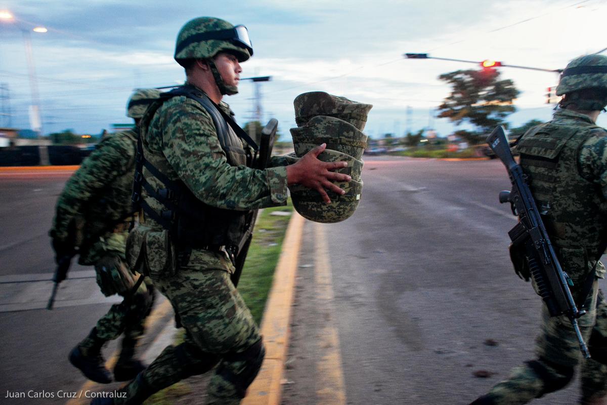 Soldados cargan los cascos y las armas de los cinco militares que murieron al ser emboscados por un comando de sicarios el 30 de septiembre del 2016, a la salida norte de ésta ciudad. En el ataque otros 10 militares resultaron heridos, así como un paramédico de la Cruz Roja. El convoy militar custodiaba una ambulancia de la Cruz Roja la cual trasladada a un hospital a un detenido que resultó herido horas antes durante otro enfrentamiento en el municipio de Badiraguato. (FOTO: Juan Carlos Cruz / Contraluz)
