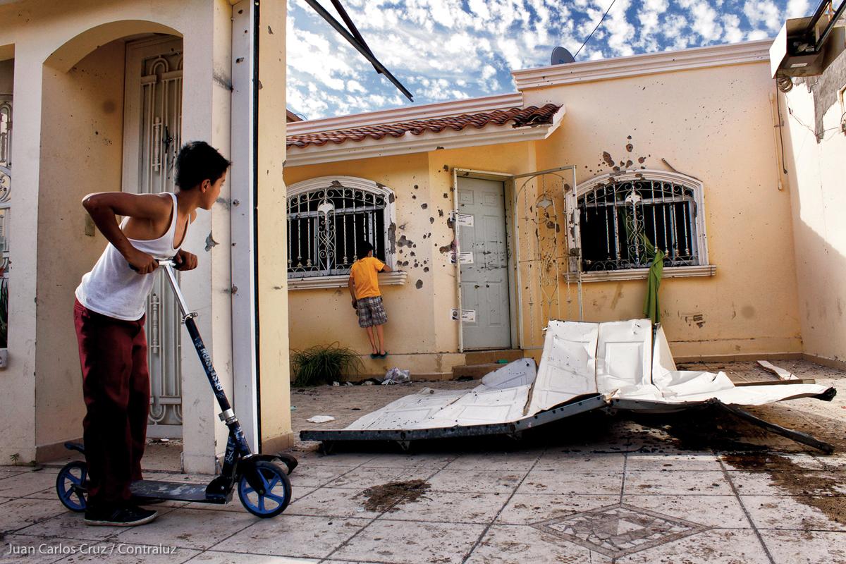 Dos niños observan la casa en donde el 20 de abril del 2015 se registró un fuerte enfrentamiento entre presuntos secuestradores, policías y militares, en el sector de Cañadas de Culiacán, Sinaloa. Durante el enfrentamiento murió la persona que se encontraba secuestrada y dos de los presuntos secuestradores. Fueron detenidos siete integrantes de la banda, entre los que se encontraba un sobrino del extinto narcotraficante Amado Carrillo Fuentes, alias El Señor de los Cielos, líder del Cártel de Juárez. (FOTO: Juan Carlos Cruz / Contraluz)