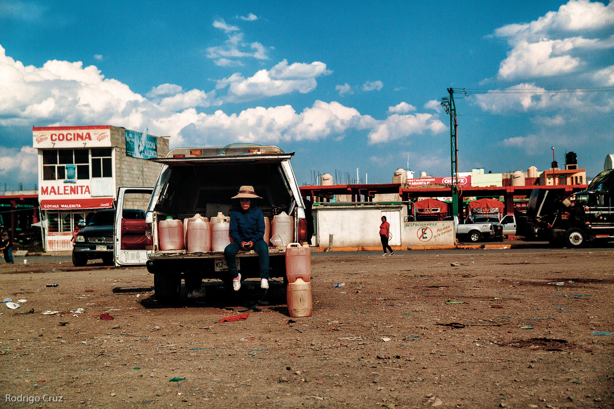 Una mujer vende gasolina robada de ductos que conectan Minatitlán, Veracruz, con la Ciudad de México en Huixcolotla, marzo de 2017. Organizaciones criminales crearon redes de robo de combustible que operan en las zonas de ductos cobijadas por autoridades con altos márgenes de ganancias. (FOTO: Rodrigo Cruz)