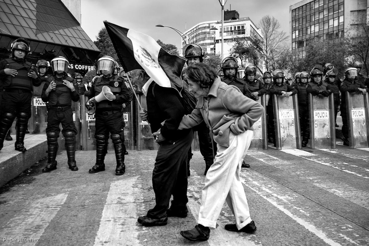 Una pareja de ancianos pasa frente al cuerpo de granaderos de la Ciudad de México, durante las protestas en contra de las reformas planteadas al congreso por el presidente Enrique Peña Nieto, el 18 de septiembre de 2013.  (FOTO: Pepe Jiménez)