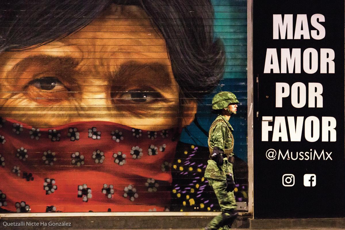 Una mujer soldado del Ejército mexicano camina por la calle de 20 de Noviembre en el centro Histórico en la madrugada previa al desfile militar conmemorativo del aniversario de la independencia de México, el 16 de septiembre de 2018. Atrás de ella, un mural sobre una mujer zapatista parece observar su paso. Fotografía: Quetzalli Nicte Ha González